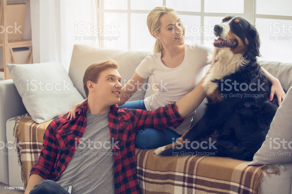 Young man and woman with dog at home