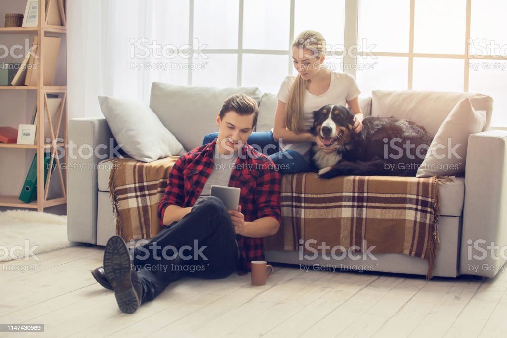 Young man and woman with dog at home browsing digital tablet