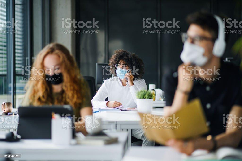 Jonge mensen met gezichtsmaskers terug op het werk of school in bureau na sluiting. - Royalty-free Arbeidsveiligheid Stockfoto