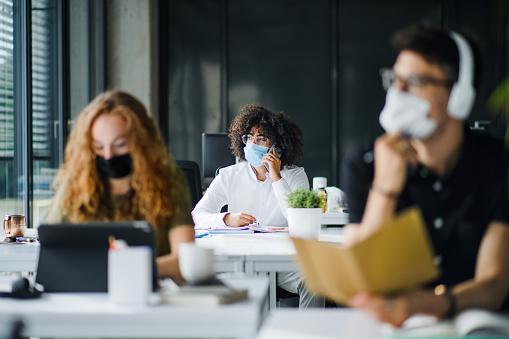 Jonge Mensen Met Gezichtsmaskers Terug Op Het Werk Of School In Bureau Na Sluiting Stockfoto en meer beelden van Arbeidsveiligheid