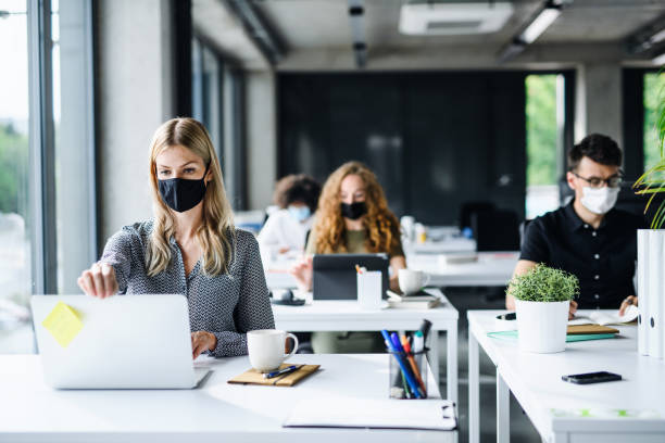 Young people with face masks back at work or school in office after lockdown. stock photo