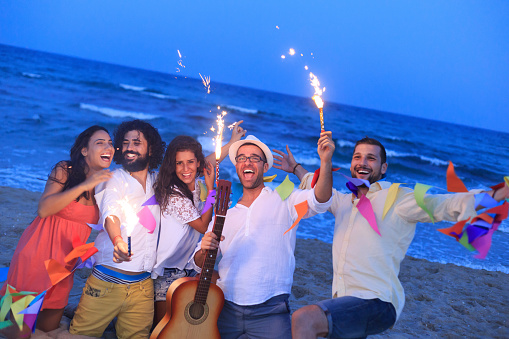 471113366 istock photo Young people with fireworks on the beach 505846298