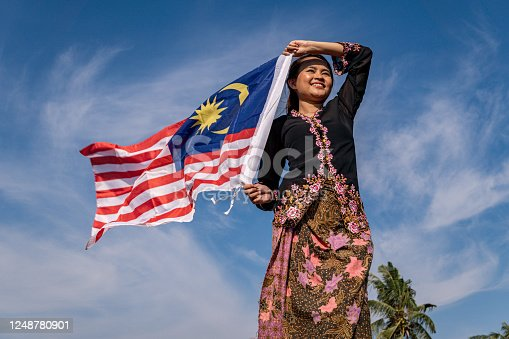 Young people with Malaysian flag at paddy field at village