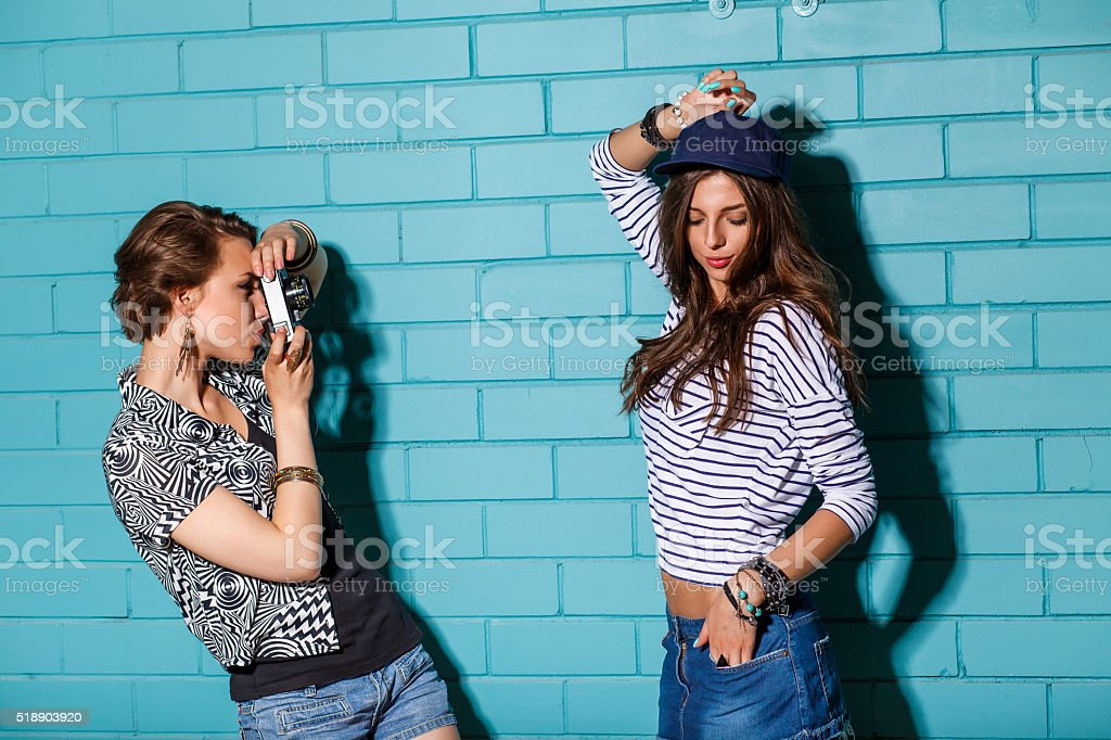 Young people with photo camera in front of blue wall stok fotoğrafı