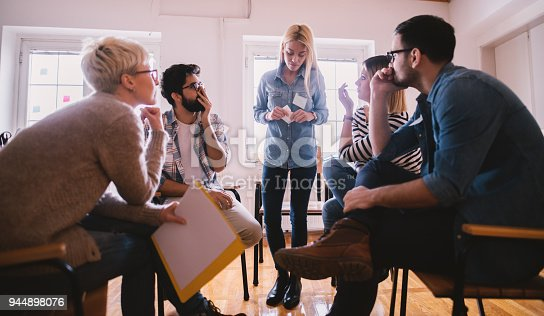 istock Young people with problems listening to their nervous female friend confession with shock reaction while sitting together on special group therapy. 944898076