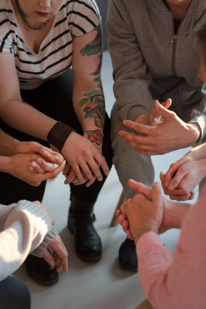 Young people with tattoos sitting in a circle during meeting of support group Young people with tattoos sitting in a circle during meeting of support group drug rehab stock pictures, royalty-free photos & images