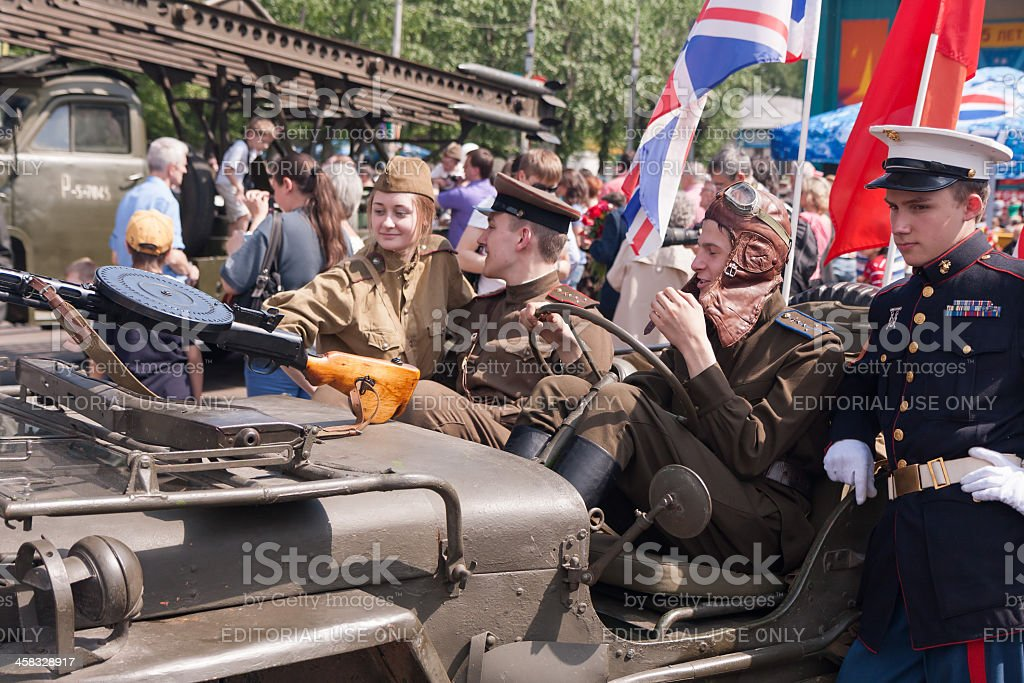 Young people with Warld War II clothes sit in GAZ-67 royalty-free stock photo