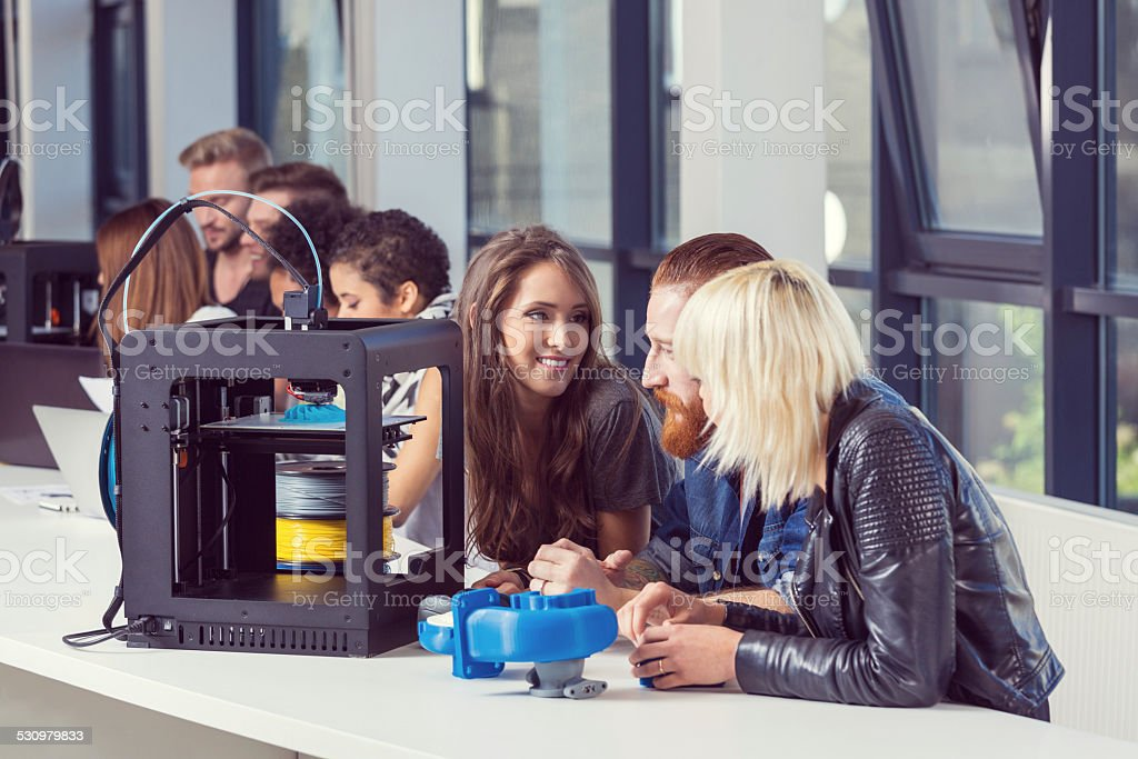 Young people working in 3D printer office Start-up Business. Group of young people using 3D printers. 2015 Stock Photo