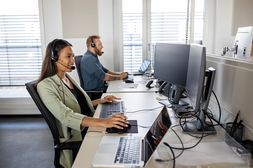 Shot of a young people working in call center. Male and female customer service agents sitting at the coworking desk wearing headset and using computer.
