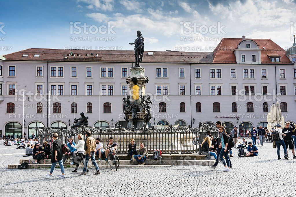 Young peple sitting at the town square of Augsburg. stock photo