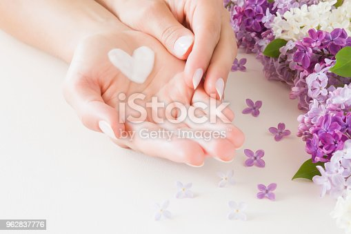 istock Young, perfect, clean woman's hands on white table. Natural herbal skin cream. Heart shape created from cream. Love a body. Beautiful branches of lilac blossoms. Colorful, fresh flowers. 962837776