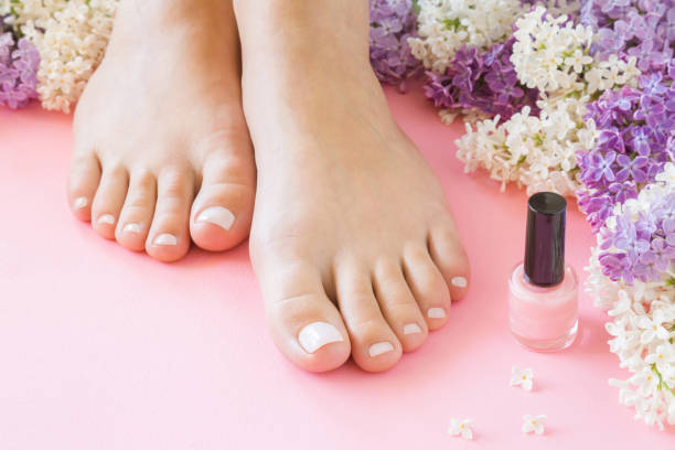 Young, perfect, groomed woman's feet with nail varnish bottle. Nails care. Manicure, pedicure beauty salon. Beautiful branches of lilac on pink background. Fresh flowers. Young, perfect, groomed woman's feet with nail varnish bottle. Nails care. Manicure, pedicure beauty salon. Beautiful branches of lilac on pink background. Fresh flowers. pink nail polish stock pictures, royalty-free photos & images