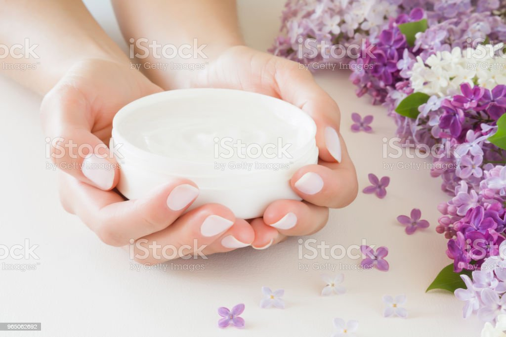 Young, perfect, groomed woman's hands holding an opened jar of natural herbal cream. Care about clean, soft and smooth skin in summer time. Beautiful branch of lilac blossoms. Colorful, fresh flowers. zbiór zdjęć royalty-free