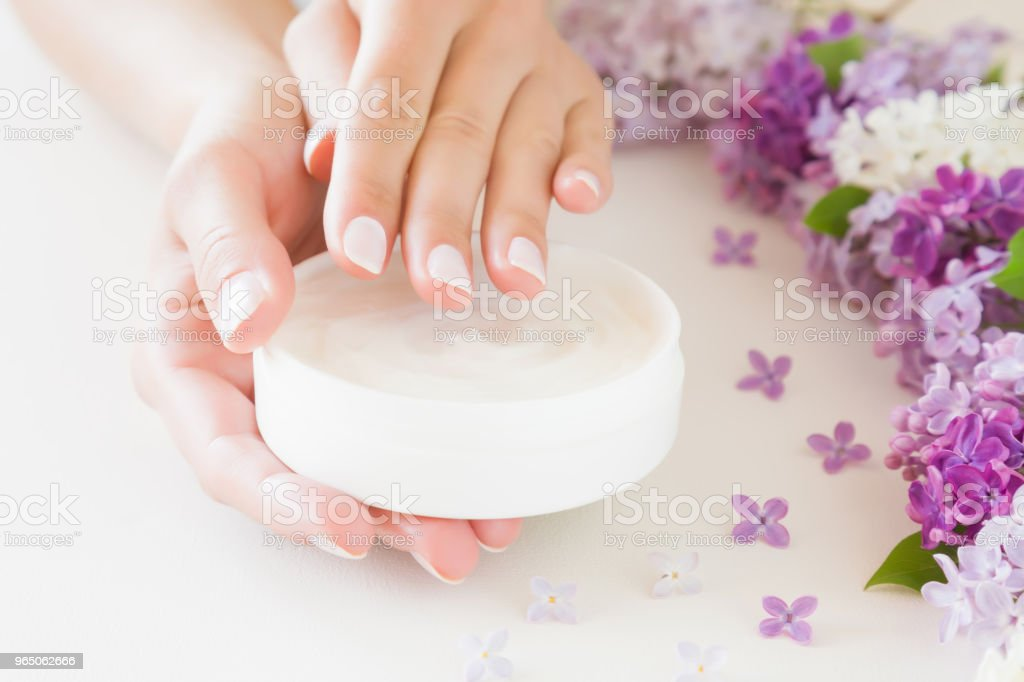 Young, perfect, groomed woman's hands using moisturizing, natural herbal cream. Care about clean, soft and smooth skin in summer time. Beautiful branch of lilac blossoms. Colorful, fresh flowers. royalty-free stock photo