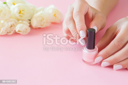 istock Young, perfect, groomed woman's hands with nail varnish bottle. Manicure, pedicure beauty salon. Beautiful roses on pastel pink table. Fresh flowers. Copy space. Empty place for text or logo. 984985382