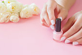 Young, perfect, groomed woman's hands with nail varnish bottle. Manicure, pedicure beauty salon. Beautiful roses on pastel pink table. Fresh flowers. Copy space. Empty place for text or logo.