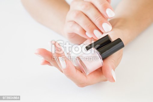 946930880istockphoto Young, perfect, groomed woman's hands with pink and white nail varnish bottles on the light gray background. Nails care. Manicure, pedicure beauty salon. 973904864