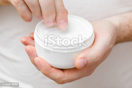istock Young, perfect man hands holding white jar and using moisturizing cream. Care about nails and clean, soft, smooth body skin. Front view. Closeup. 1134676097