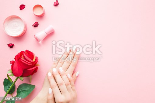 1147741037istockphoto Young, perfect woman hands with nail polish bottle, cream jars and red rose on pastel pink table. Care about nails and clean, soft, smooth skin. Empty place for text, quote, sayings or logo. Top view. 1135701726