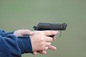 Young person firing hand gun