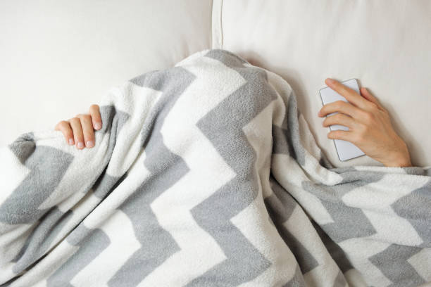 A young person lies in bed under a blanket and have a hard time waking up in the morning. stock photo