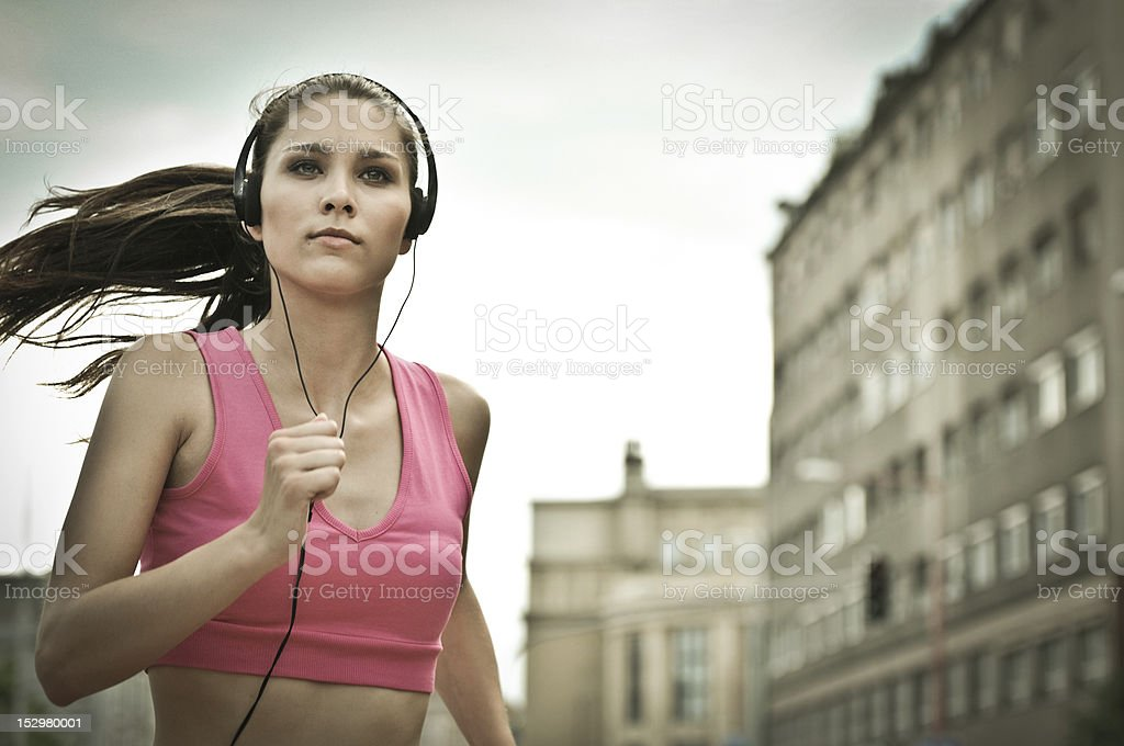 Young person listening misic running in city street royalty-free stock photo