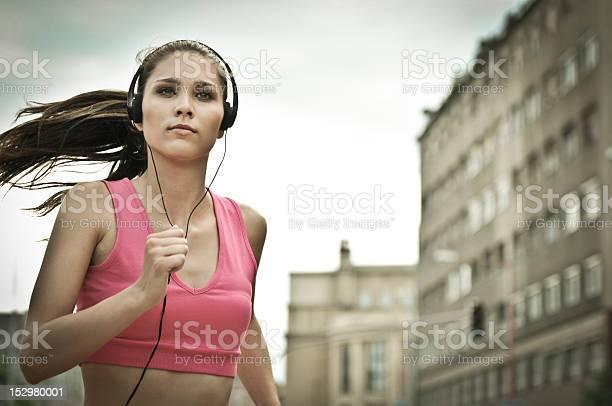 Joven Escuchando Misic Corriendo En La Calle De La Ciudad Foto de stock y más banco de imágenes de Actividad