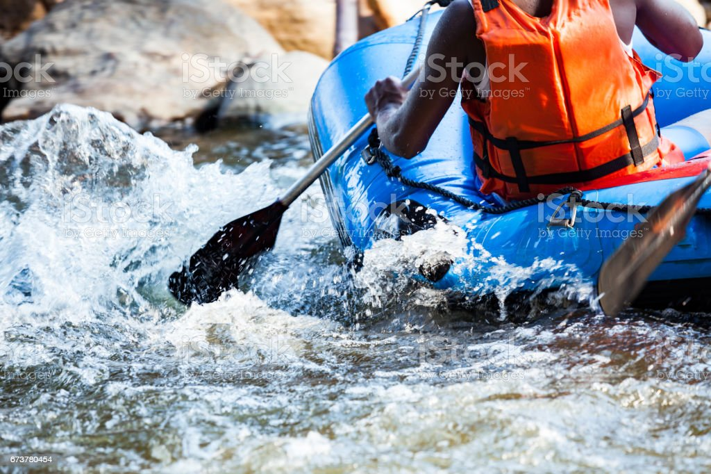 Young person rafting on the river, extreme and fun sport at tourist attraction stock photo