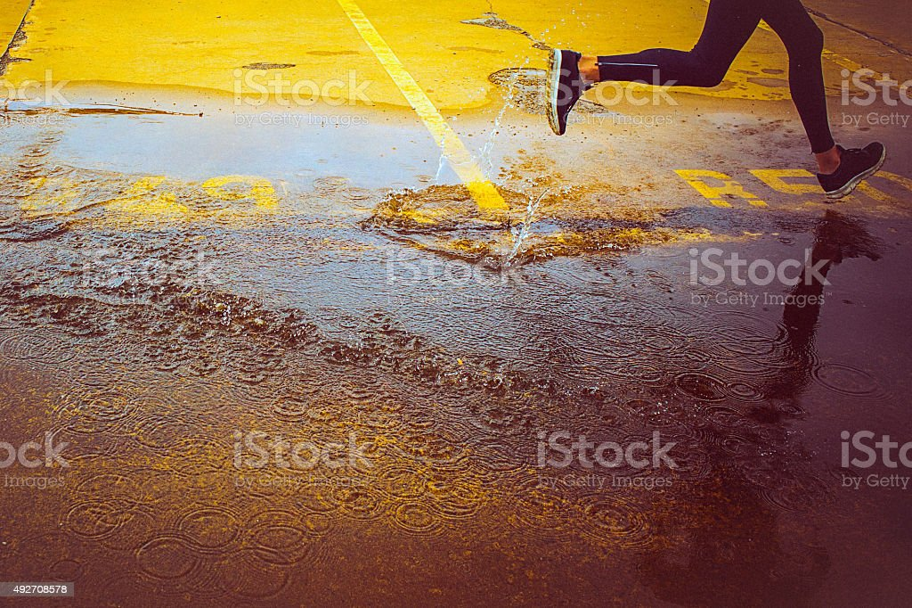 Young person running over the parking lot stock photo
