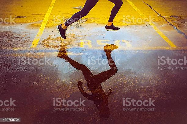 Photo of Young person running over the parking lot