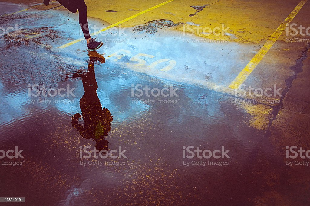 Young person running over the yellow parking lot stock photo