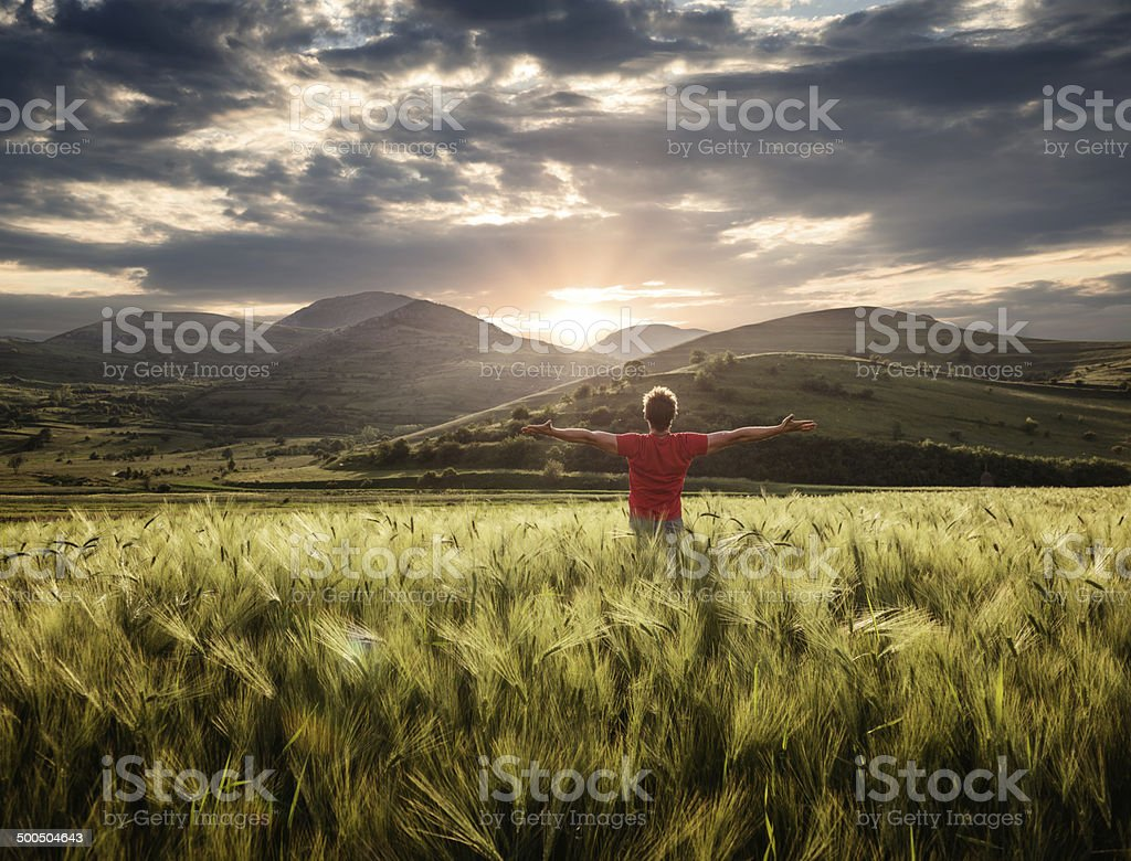 young person sitting outdoor in the weath field expressing positivity stock photo