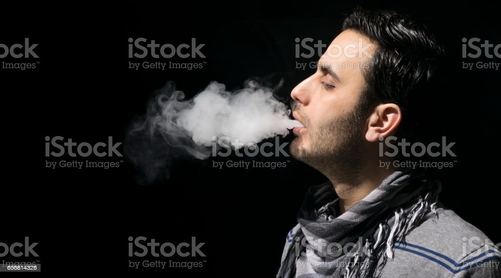 Young person vaping an e cig with lots of clouds. Isolated on a dark background. stock photo