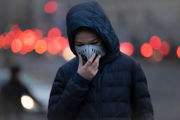 Young Person wearing Anti-Pollution Mask, Polluted Air, City Street Young Person wearing Anti-Pollution Mask, Polluted Air, City Street antipollution stock pictures, royalty-free photos & images