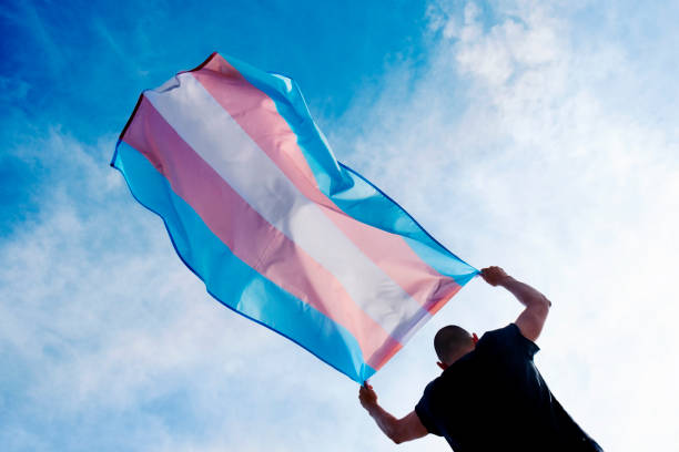 young person with a transgender pride flag stock photo