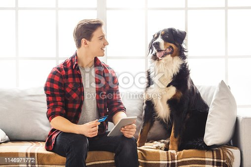 842971872 istock photo Young person with dog at home leisure 1146971772