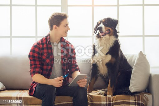 842971872 istock photo Young person with dog at home leisure 1148939692