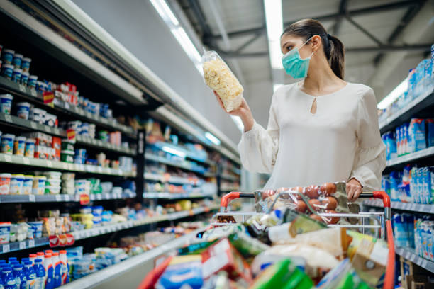 junge person mit schützender gesichtsmaske kaufen lebensmittel / lieferungen im supermarkt. vorbereitung auf eine pandemie-quarantäne aufgrund des coronavirus-covid-19-ausbruchs. die wahl der nicht verderblichen lebensmittel - konsum stock-fotos und bilder