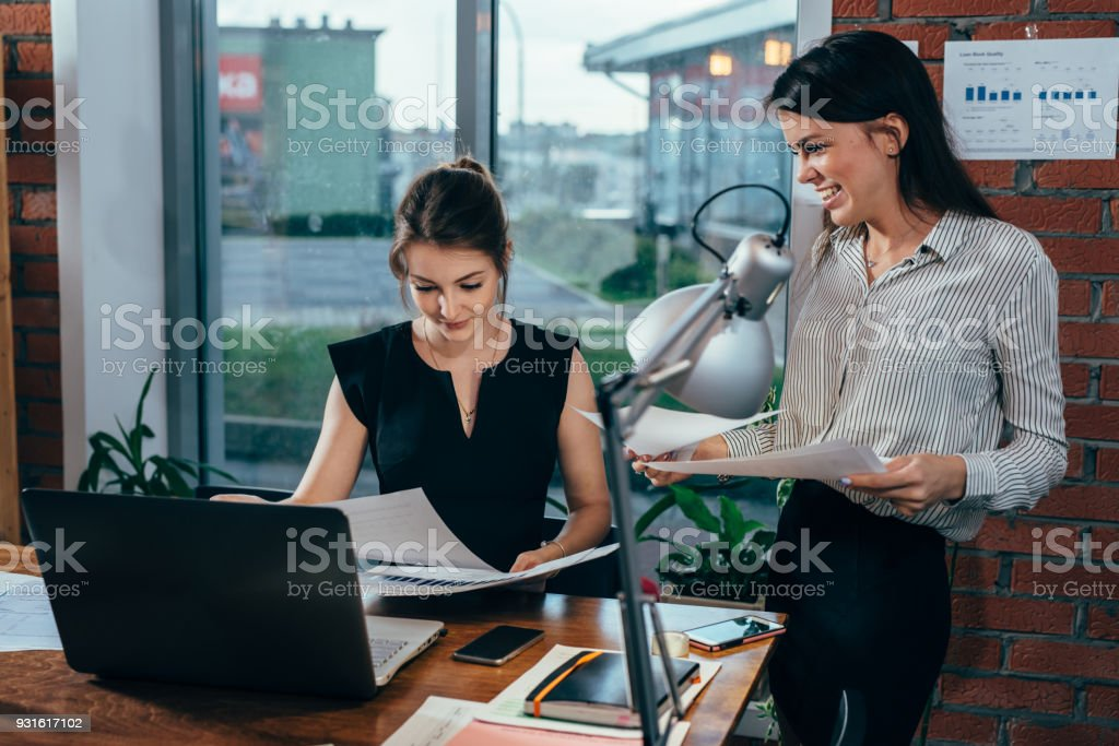 Young personal assistant discussing plans with boss in her office stock photo