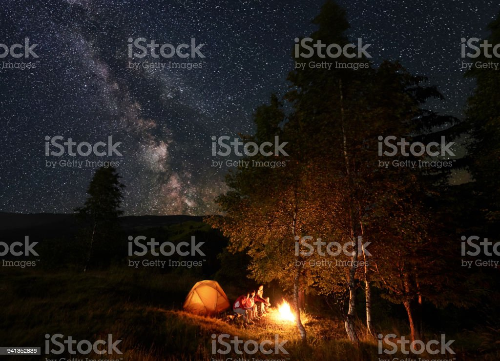 Young peson by campfire sitting on logs during night camping among trees near tent under starry sky stock photo