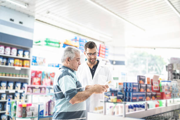 Young pharmacist helping a customer finding a medicine stock photo