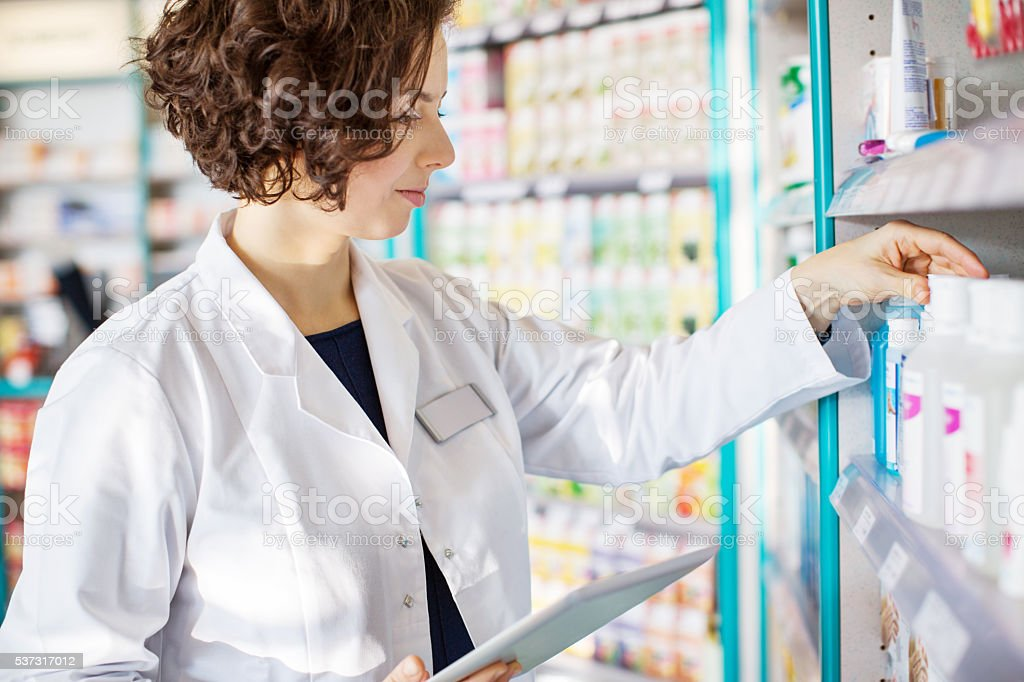 Young pharmacist with a tablet in drug store stock photo