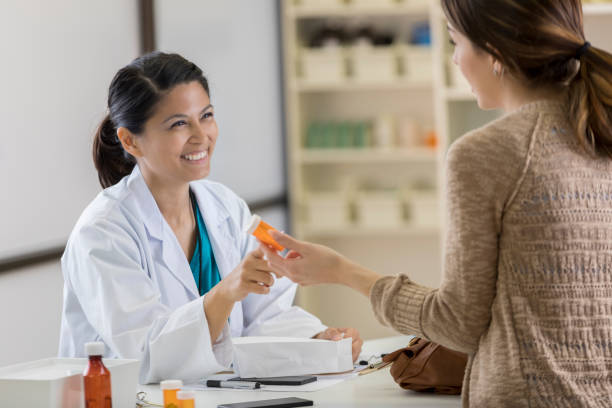 Young pharmacy customer asks pharmacist questions about medication stock photo