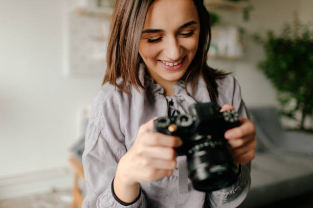Young photographer checking photos on a camera stock photo