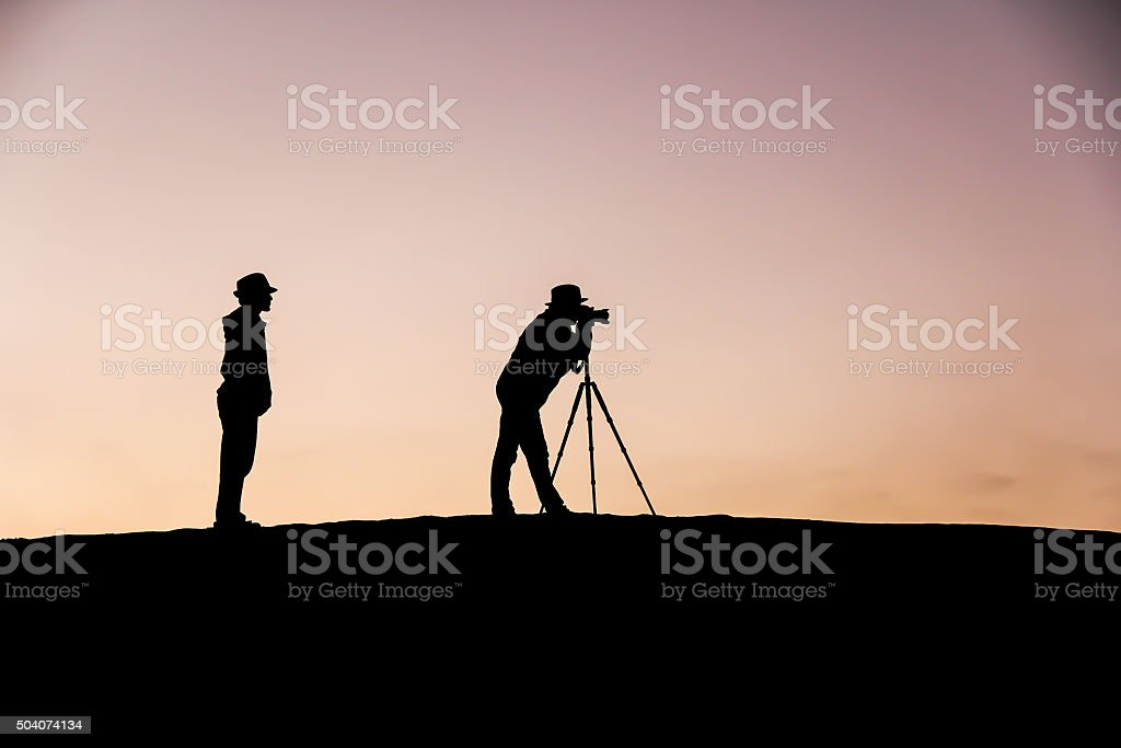 Young Photographer observing the professional photographer, Dubai Dunes stock photo