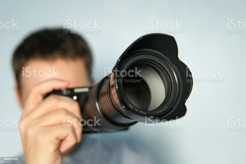 Young photographer on blue background stock photo
