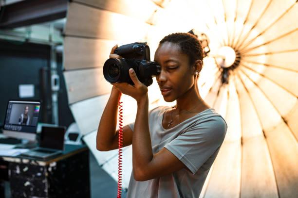 Junge Fotografen steht man vor einem reflektierenden Schirm – Foto