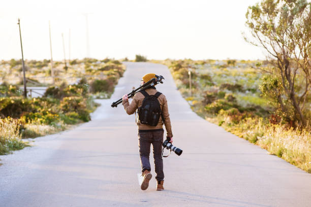 Young photographer walking on desert road with tripod on his shoulder and camera in hand stock photo