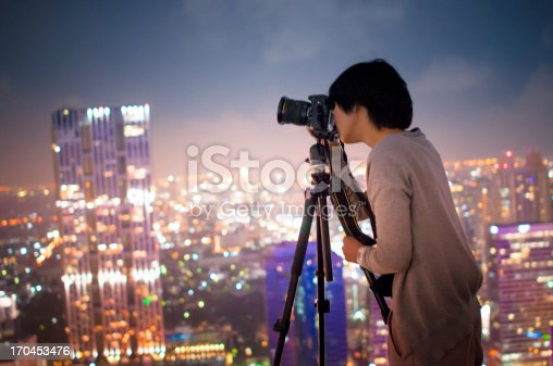 Young photographer with night light of big city .