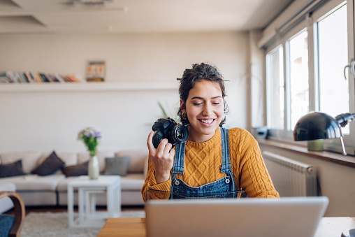 Young photographer working at her home office.